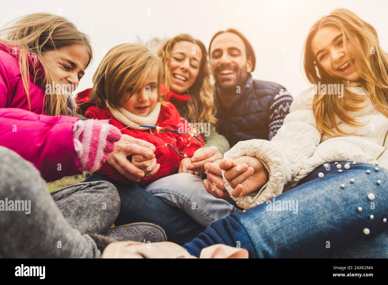 Happy family having a party outdoor celebrating with sparkler fireworks on new year's eve Stock Photo