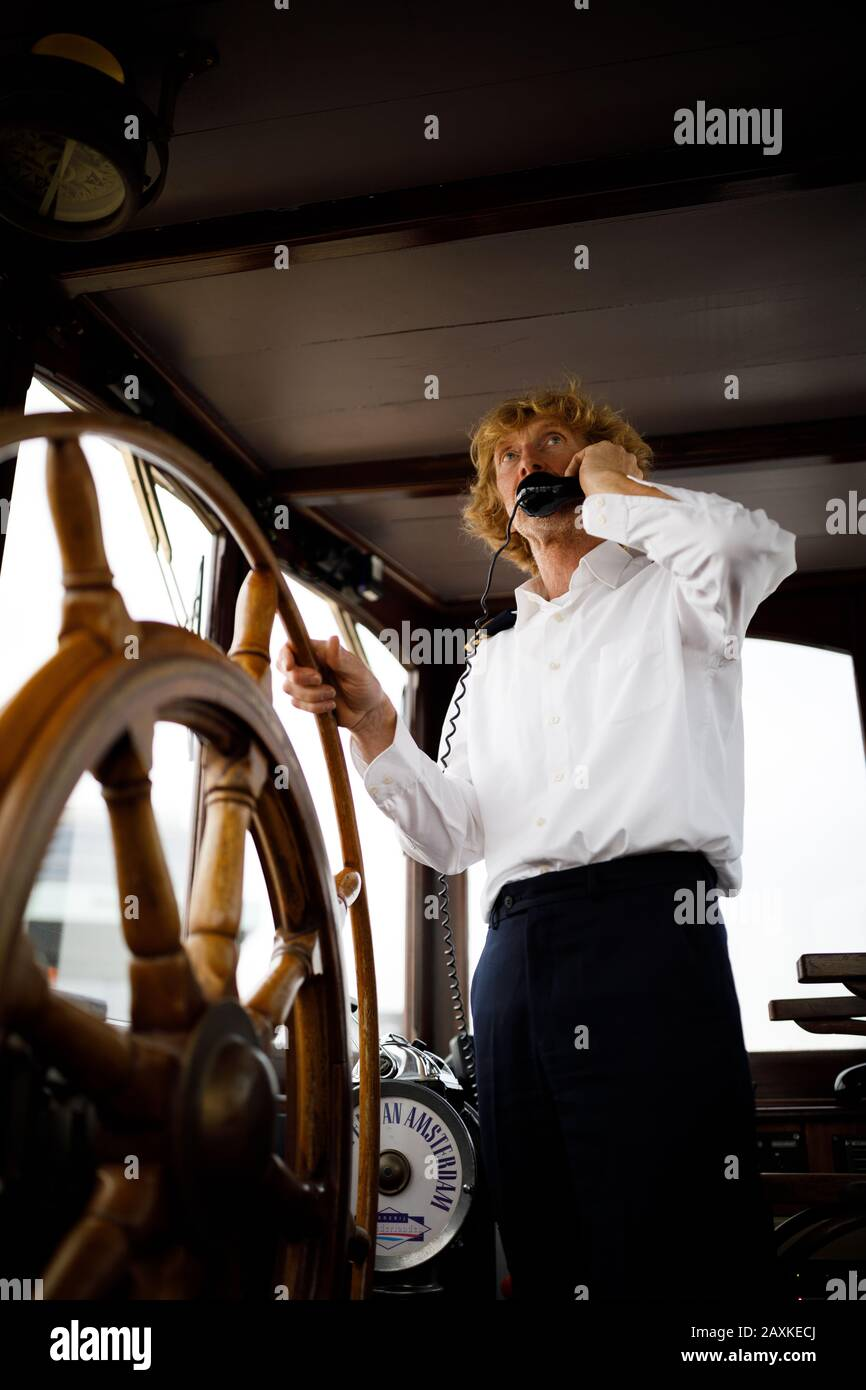 Captain Steering A Vintage Boat Standing Behind A Wooden Wheel Stock Photo Alamy