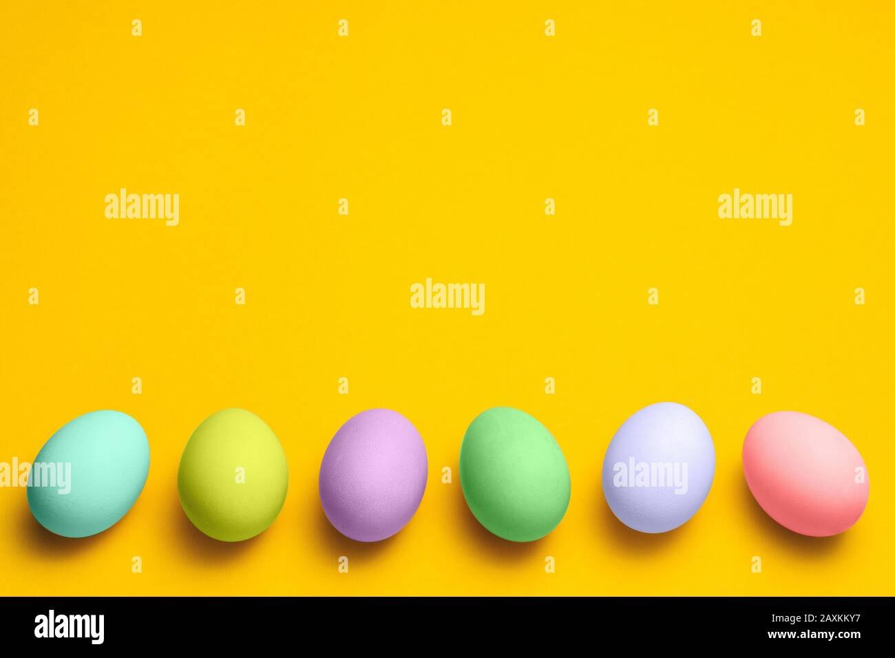 easter eggs painted in pastel colors on a yellow background with copyspace. easter advertise minimalist concept design Stock Photo