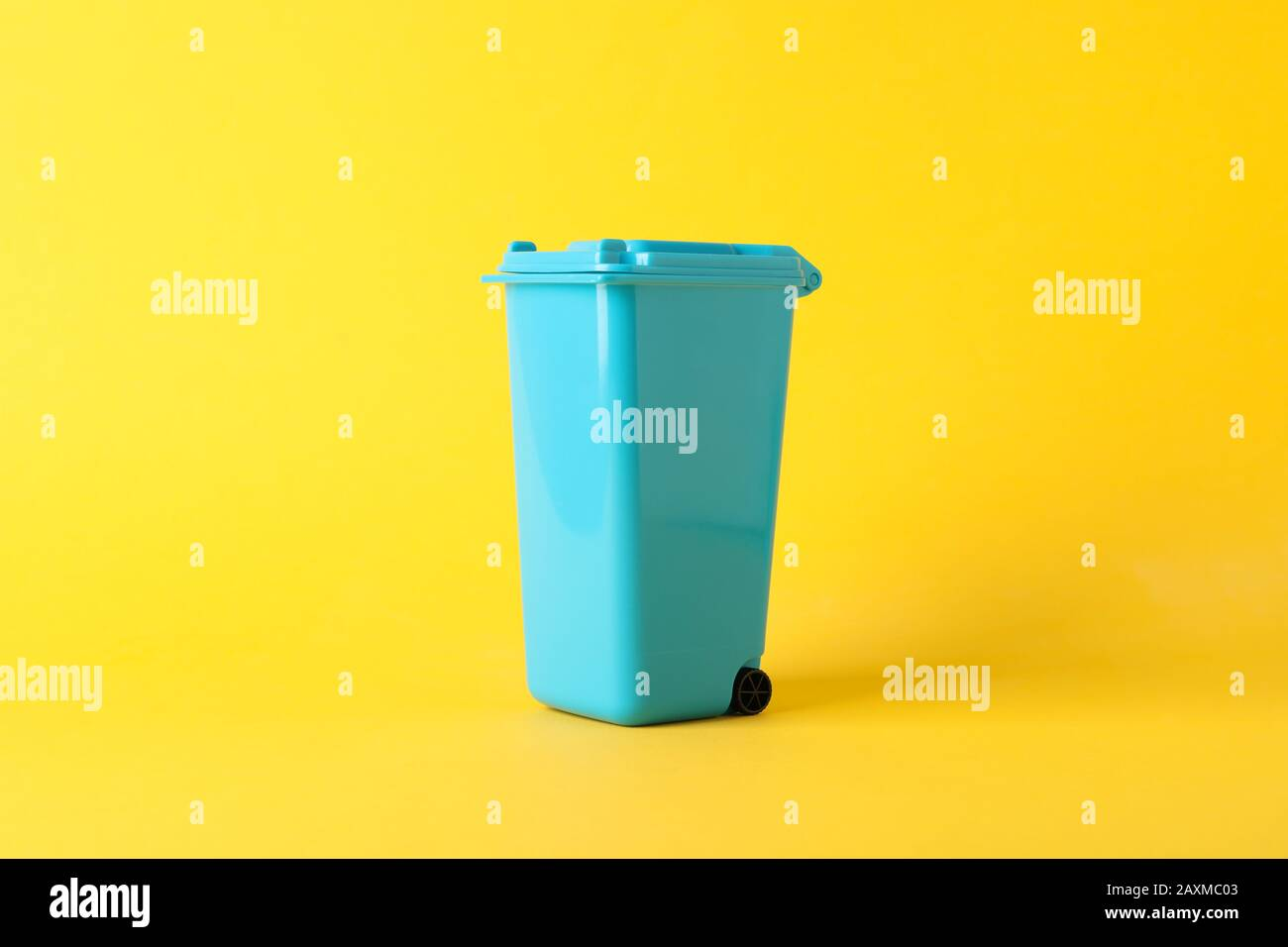 Blue recycle bin on yellow background, space for text Stock Photo
