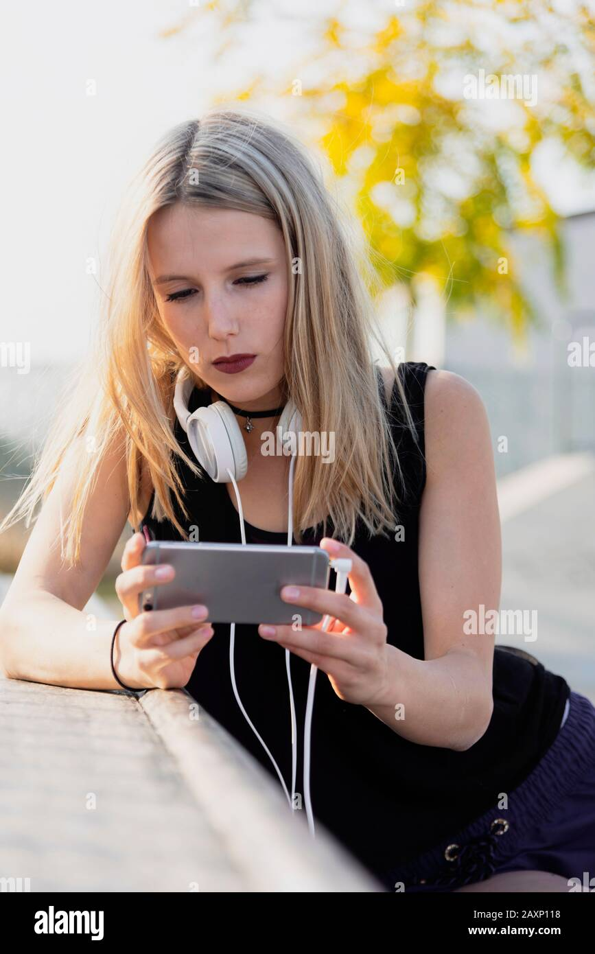 Young woman in the skate park while the music hearing Stock Photo