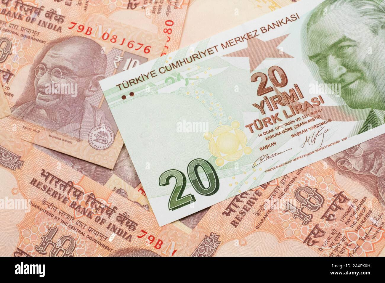 A close up image of a green twenty Turkish lira bank note on a background of Indian ten rupee bank notes in macro Stock Photo