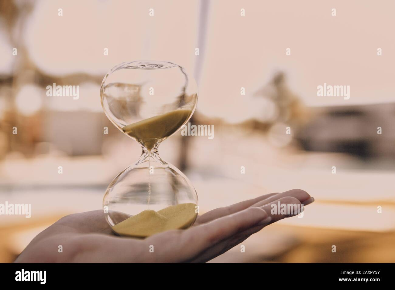 Hourglass in a female hand on a blurry light background, a symbol of the passage of time and the implementation of important life matters Stock Photo