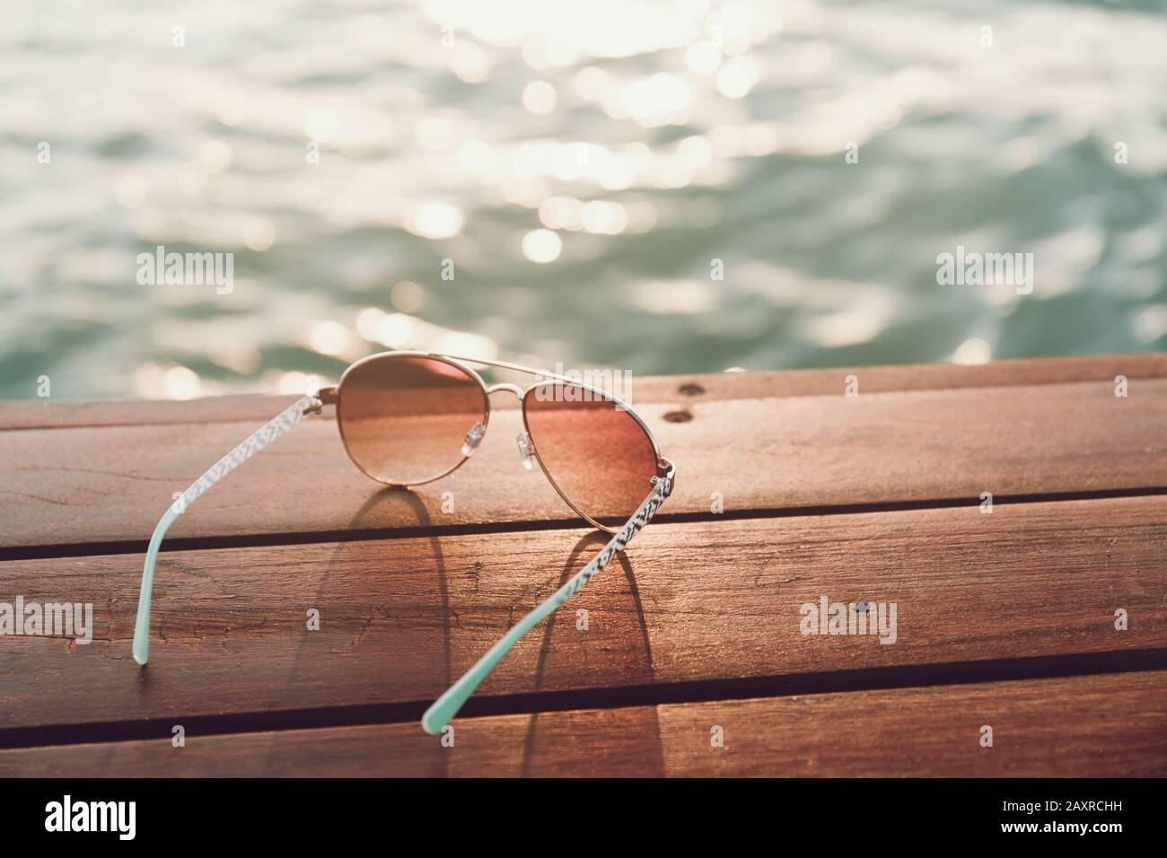 Sunglasses at the pier at sunset. Horizontal Stock Photo