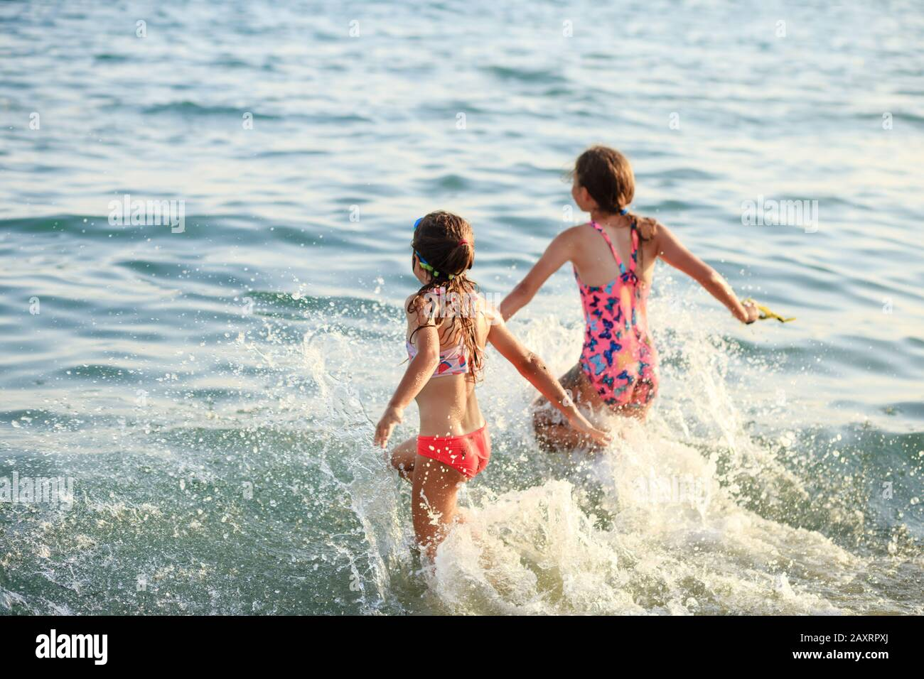 Two Cute Little Girls playing with waves by the Sea at sunset.  Summer Sunny Day, Ocean Coast, happy Kids concept,  soft focused Stock Photo