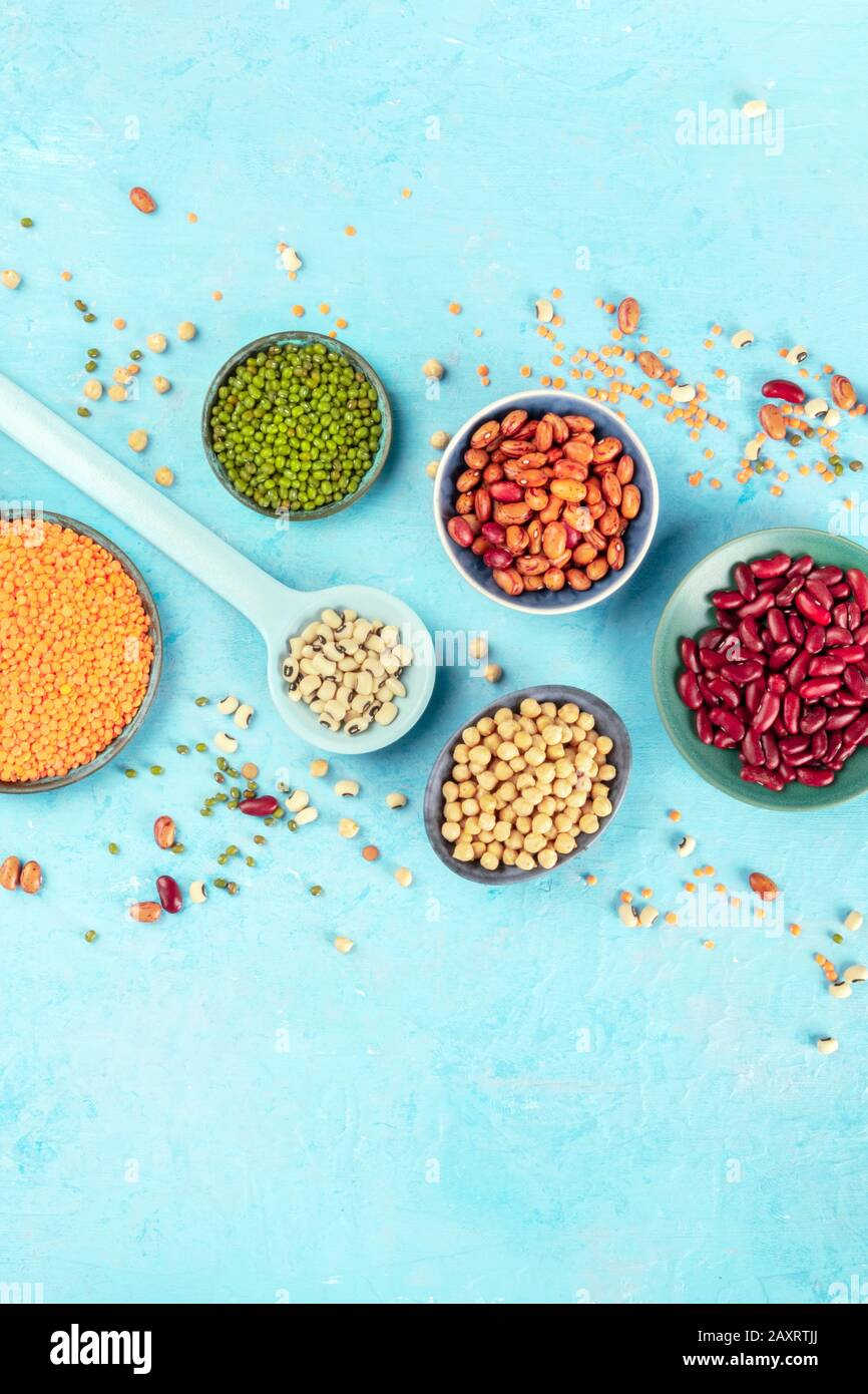 Various legumes flat lay. Different pulses, shot from above on a blue background with a place for text. Red beans, lentils, chickpeas, soybeans Stock Photo