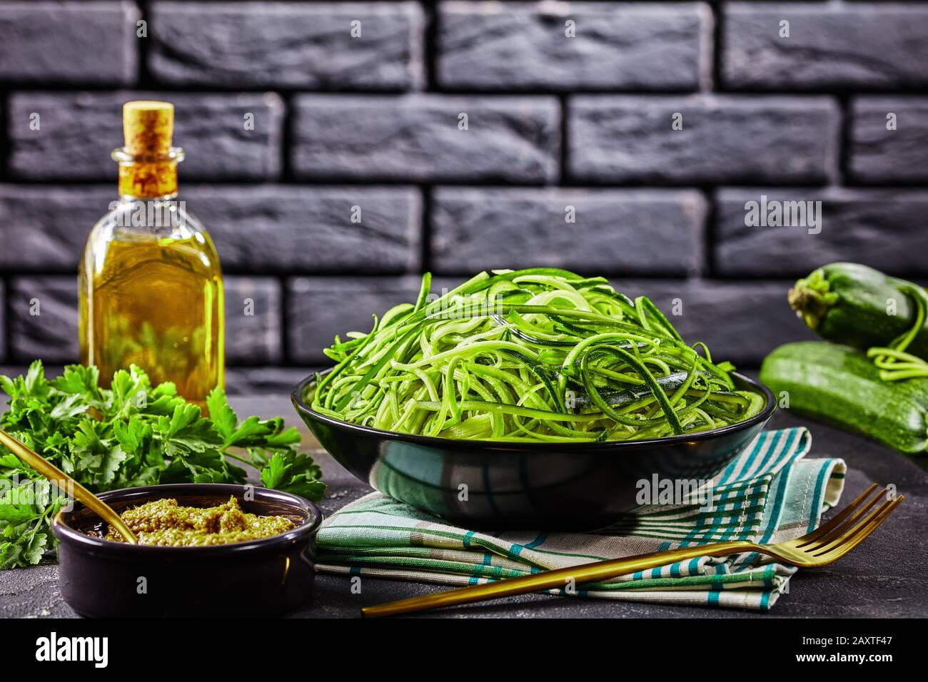 spiralized Zucchini spaghetti, zoodles in a black bowl on a grey concrete table with sauce pesto and ingredients with a brick wall at the background, Stock Photo