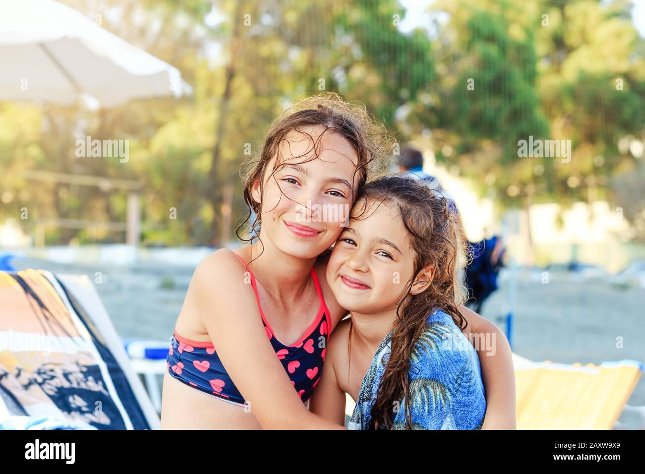 Two Cute Little Girls hugging and smiling at the Seaside at  Summer Sunny Day, Ocean Coast, happy Kids concept Stock Photo