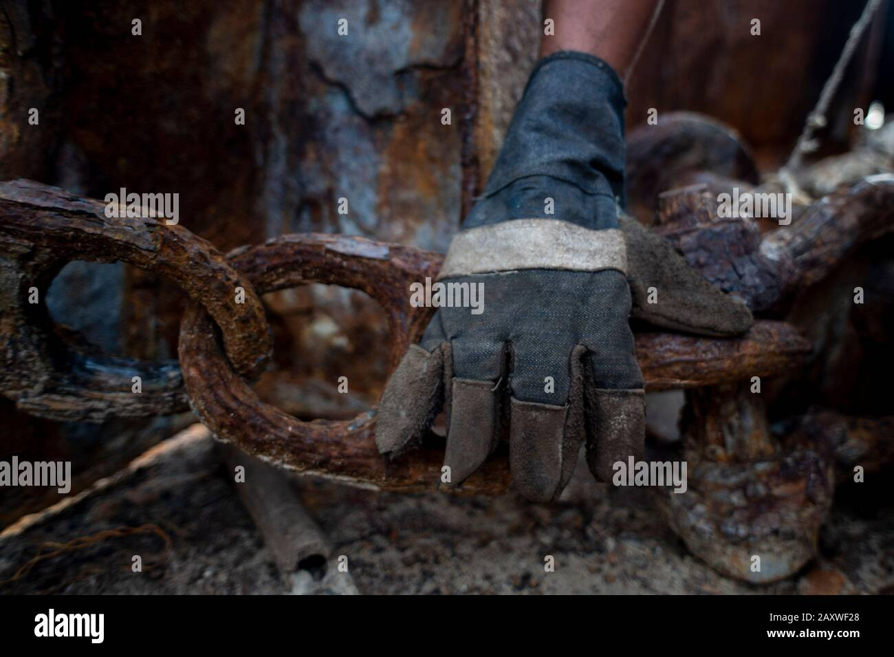 (200213) -- JAKARTA, Feb. 13, 2020 (Xinhua) -- A worker catches a rusty chain at a ship breaking yard in Cilincing of Jakarta, Indonesia, Feb. 13, 2020. Ship breaking is a recycling process in which vessels are taken apart and sold as scrap metal. (Xinhua/Agung Kuncahya B.) Stock Photo