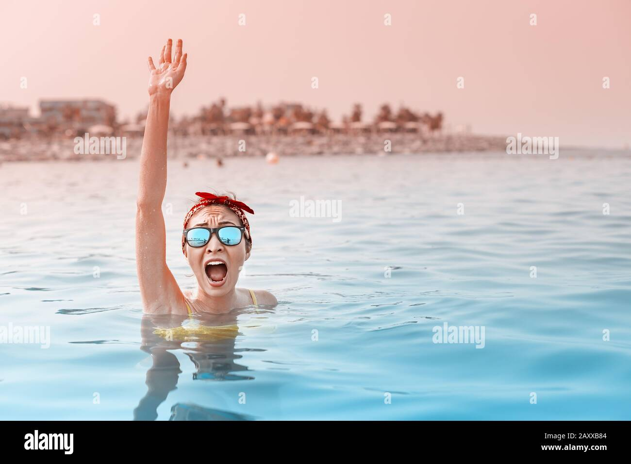Desperate asian woman swimming in the sea and asking for help, shouts and raises her hand. Concept of accidents and drowning in water, lifeguard on th Stock Photo
