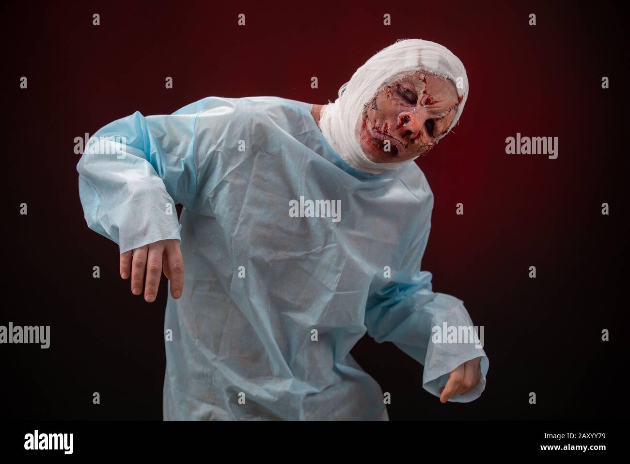 Crazy zombie horror make up. Person in blue madical shirt and bandaged head. Scars, deep scratches realistic art make-up. head is re-banded bandage Stock Photo