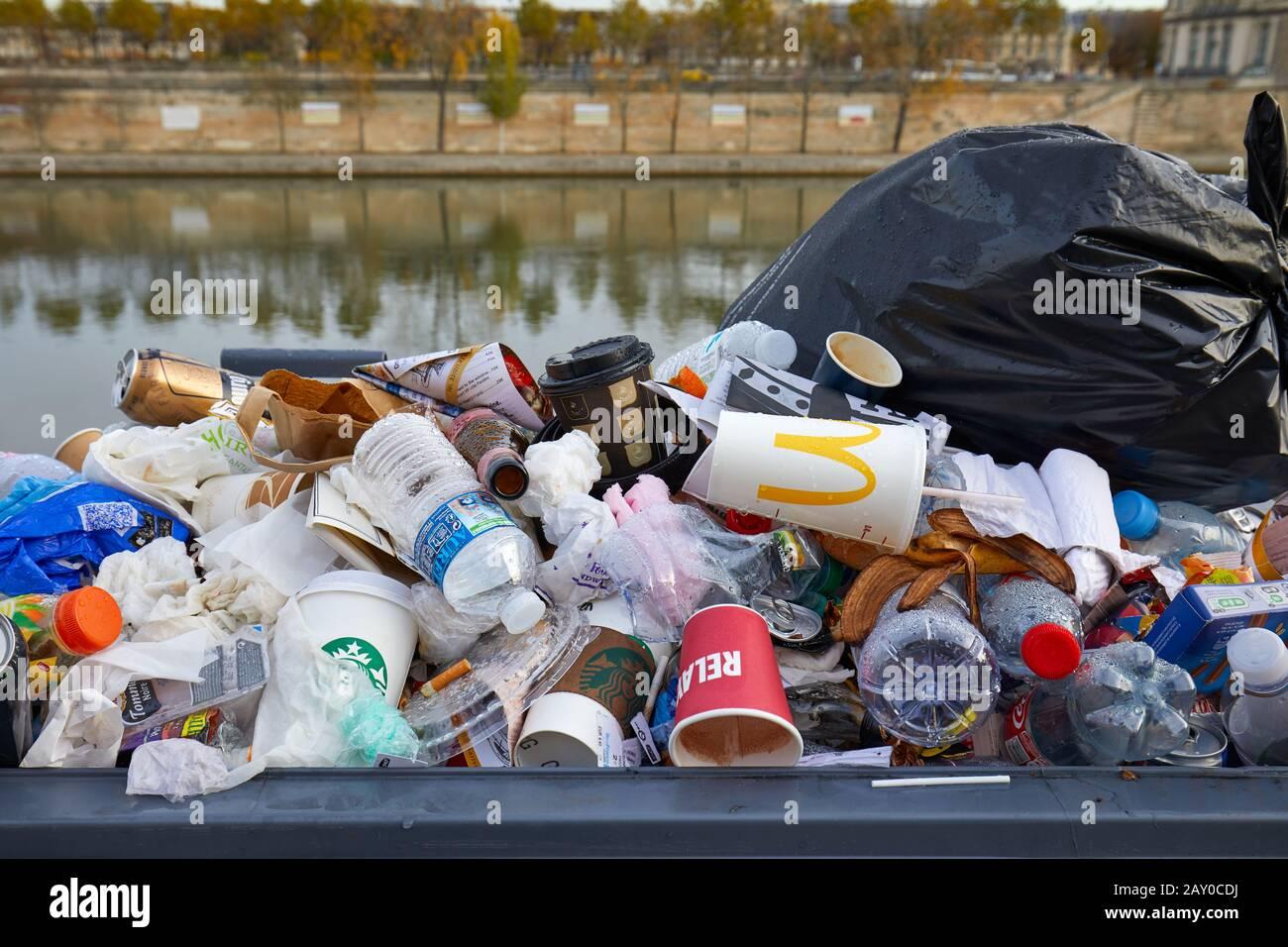 PARIS - NOVEMBER 8, 2019: Full garbage basket with colorful rubbish in Paris Stock Photo