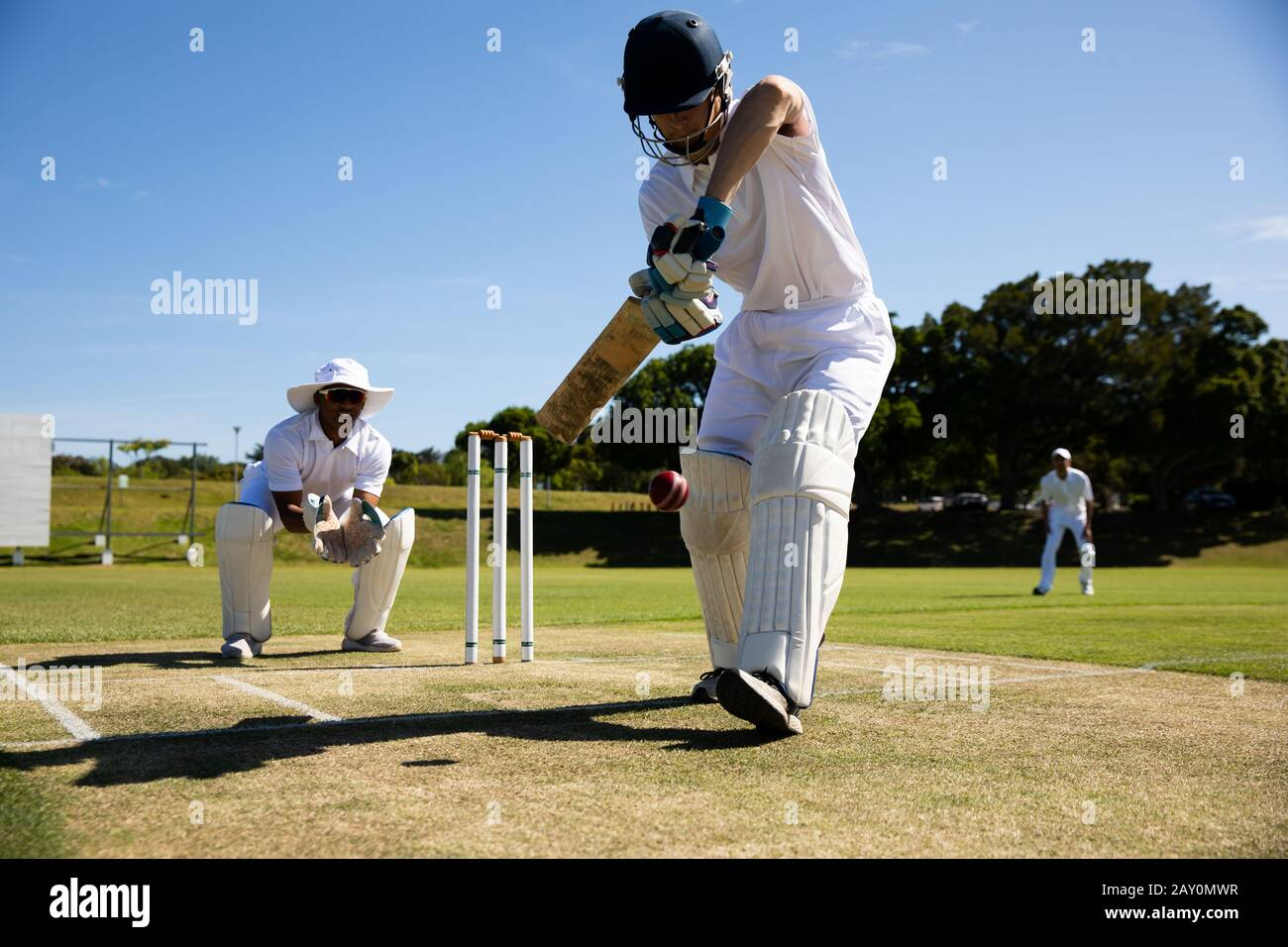 Cricket player shooting in the ball Stock Photo