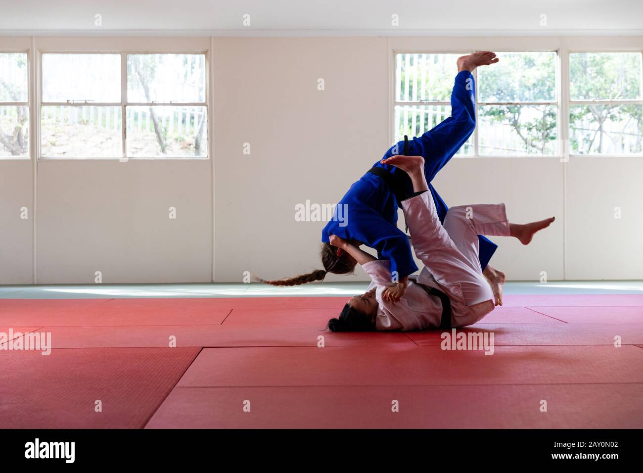 Judokas practicing judo during a sparring in a gym Stock Photo