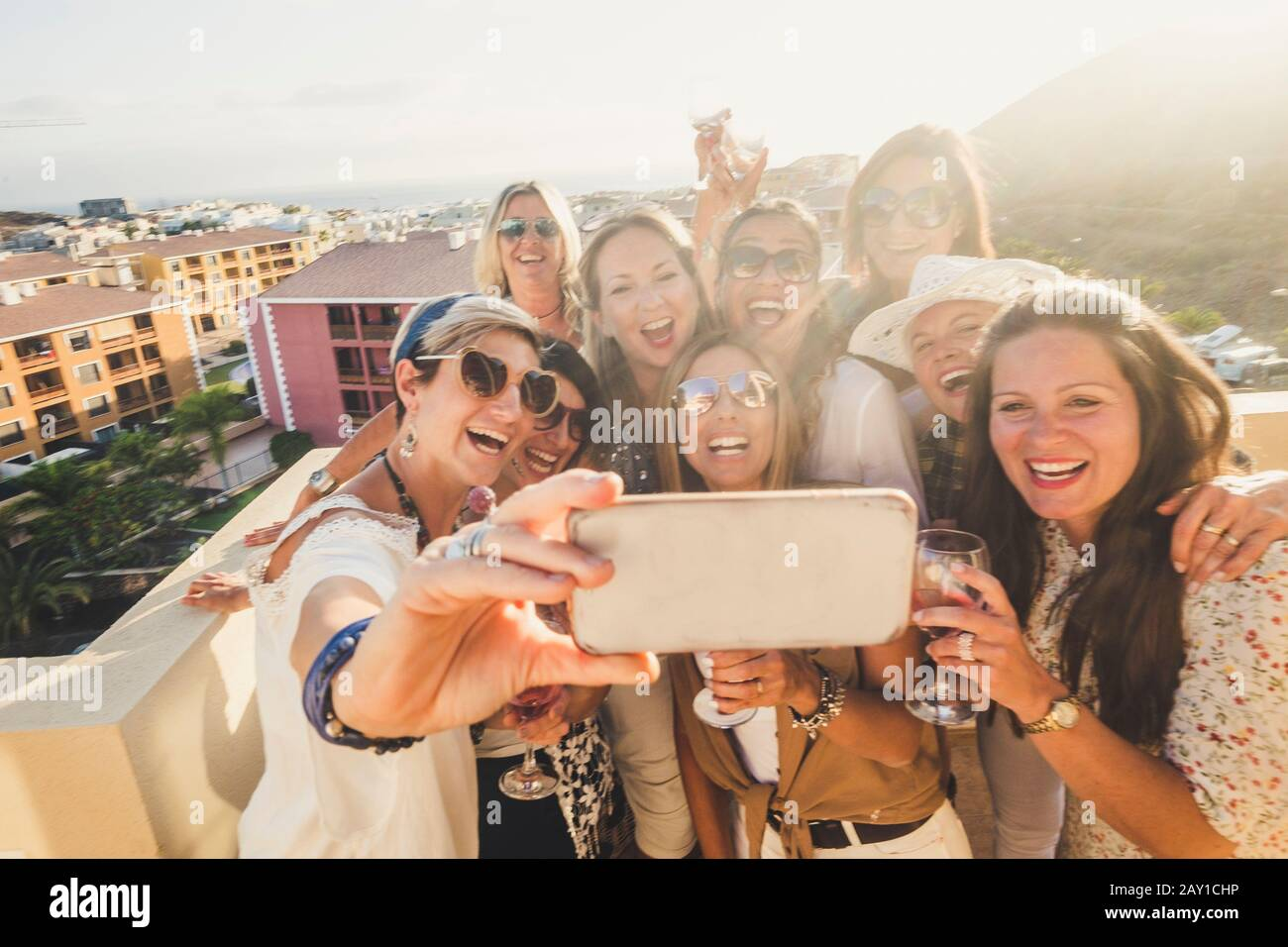 Group of happy and cheerful young women have fun in party together outdoor taking selfie picture with phone - people celebrate with wine and toasting Stock Photo