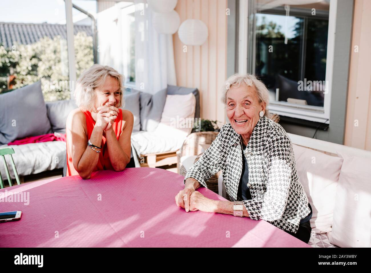 Smiling women sitting in front of house Stock Photo