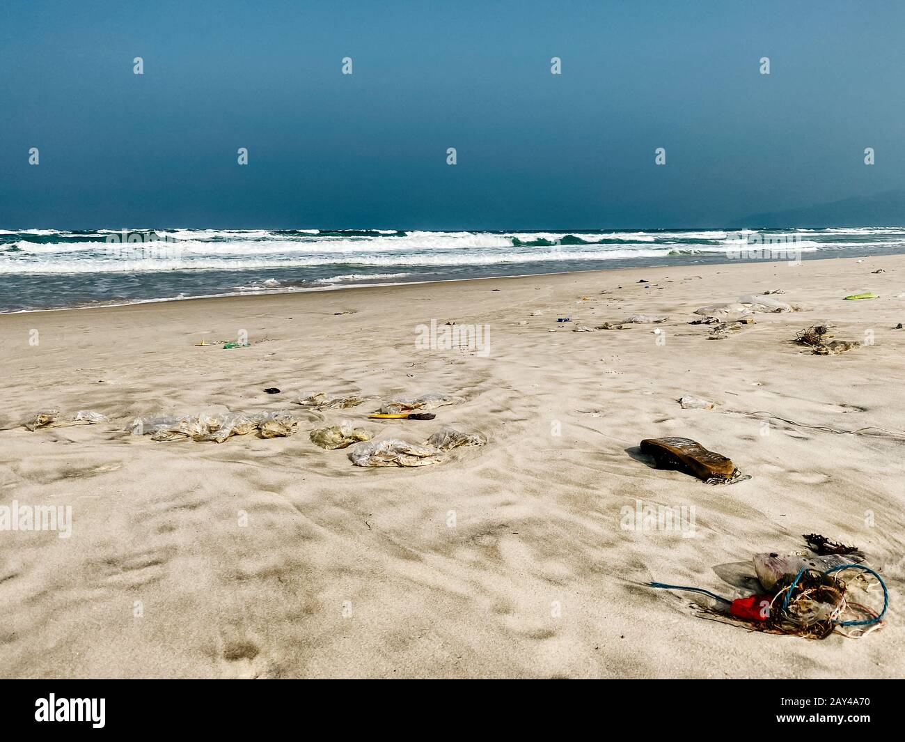 Plastic bottles and other rubbish thrown on the sandy seashore, trash on the sea beach. ecological problem. Environmental pollution. Dirty sandy beach Stock Photo