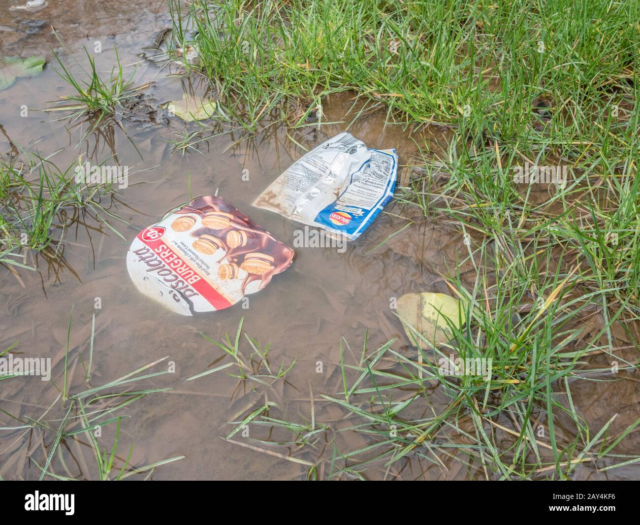 Empty plastic food packaging floating in water puddle after heavy winter rain. Metaphor war on plastic, plastic litter, problem food packaging. Stock Photo