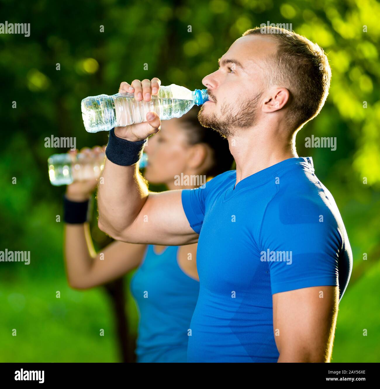 Man And Woman Drinking Water From Bottle After Fitness Sport