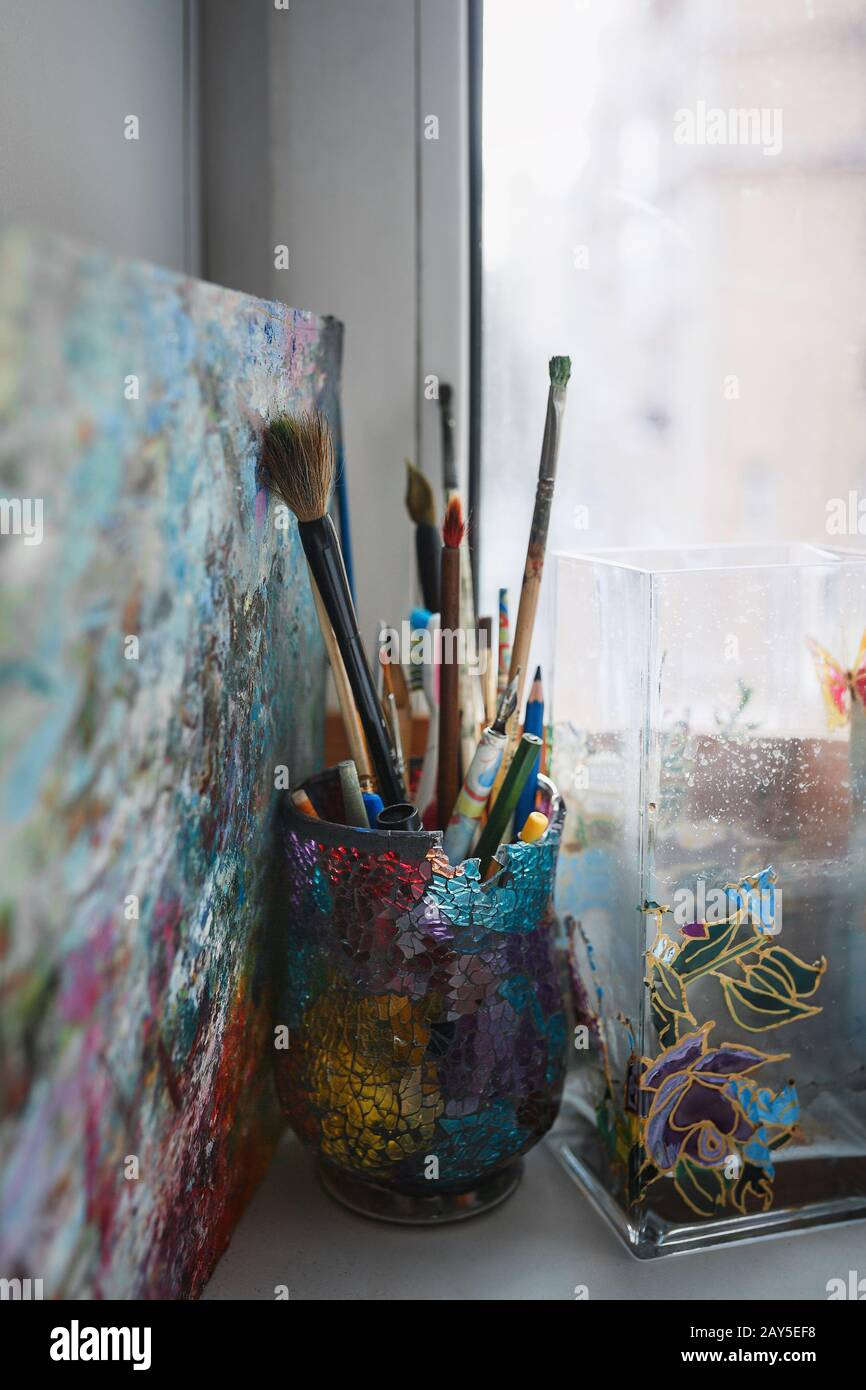 A variety of artist brushes and pencils are on the windowsill in a beautiful glass made of colored glasses.  Stock Photo