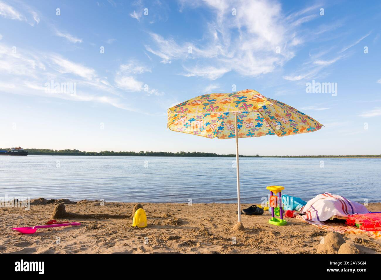 Parasol on the river bank, under which the scattered items and toys Stock Photo