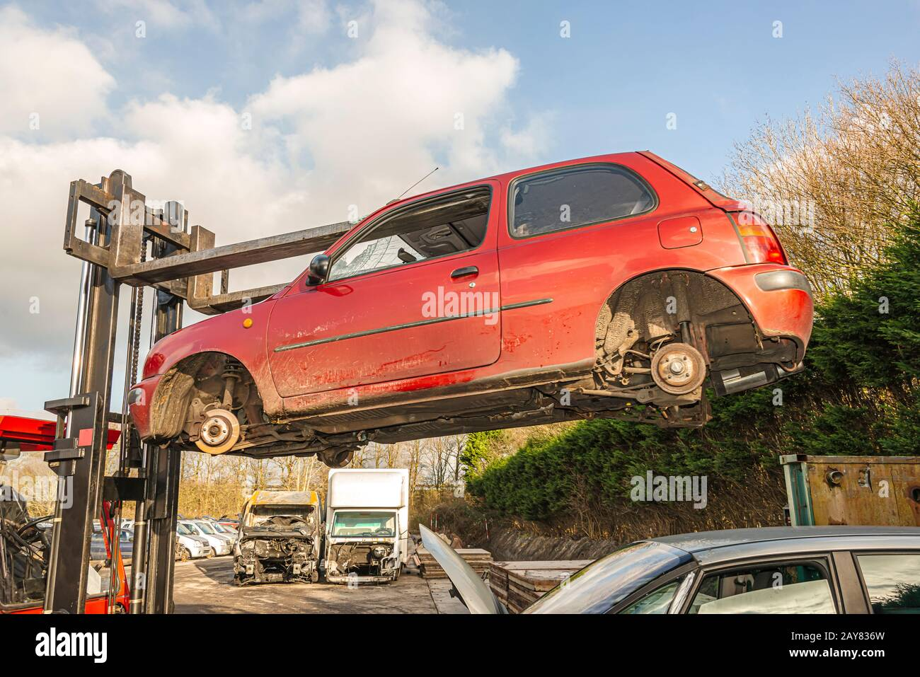 car wreck hanging from a lift truck high in the air on a dismantling site Stock Photo