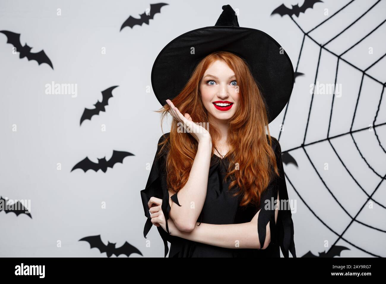 Halloween Concept - Beautiful caucasian witch surprising with something over grey background. Stock Photo