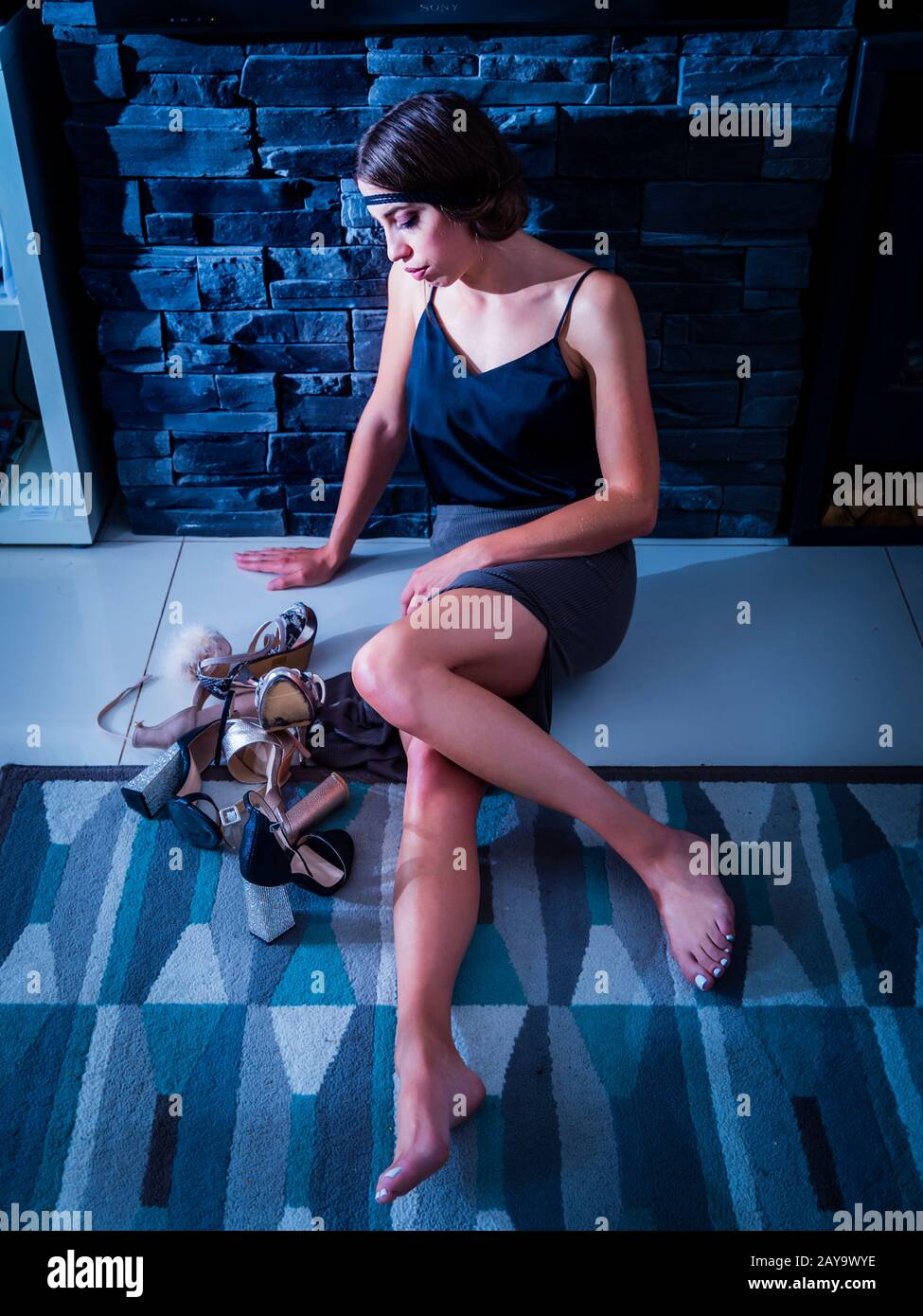 Tough decision choosing the right shoes young woman sitting reclined on floor inclined on wall looking down at bunch many several pairs of shoes Stock Photo