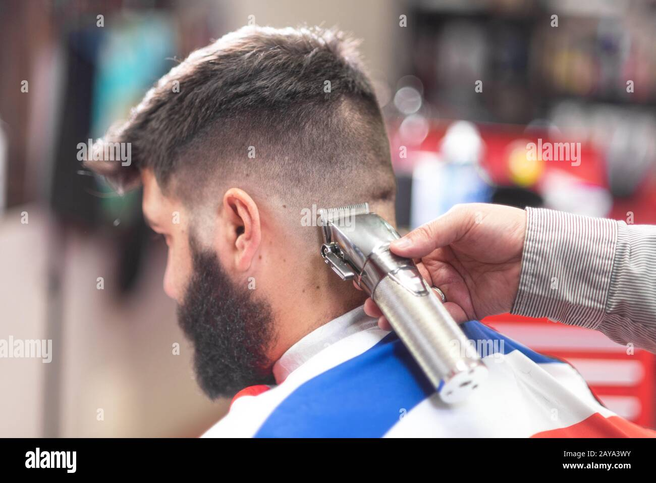 Handsome bearded man, getting haircut by barber, with electric trimmer at barbershop. Stock Photo