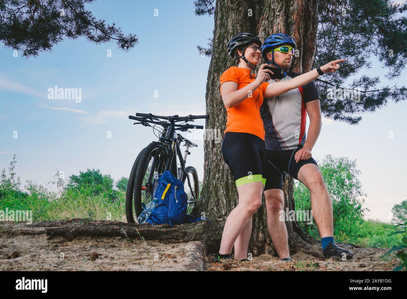 Happy couple searching on map in smartphone destination. man and woman in helmets traveling mountain biking over rough terrain. Stock Photo