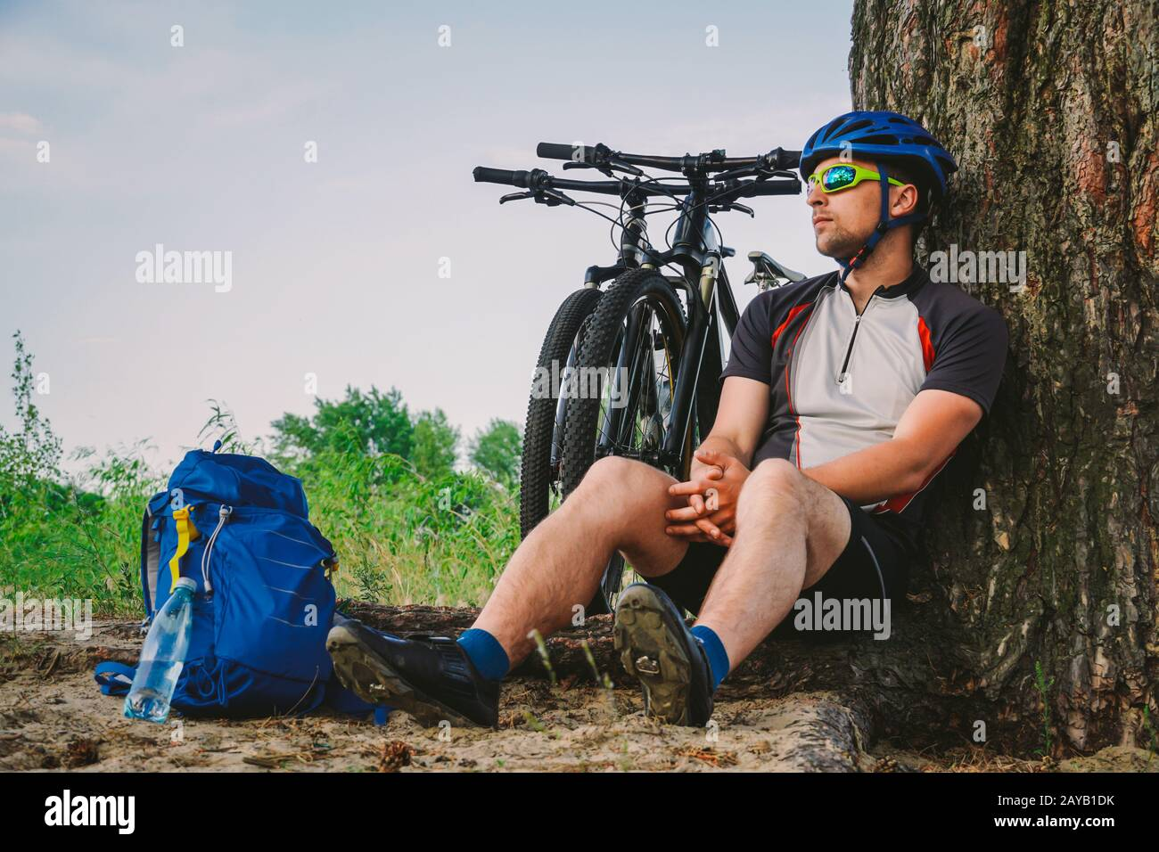 male mountain biker resting on bike ride, sitting on ground under a tree with his mountain bike, stands next to him, enjoying th Stock Photo