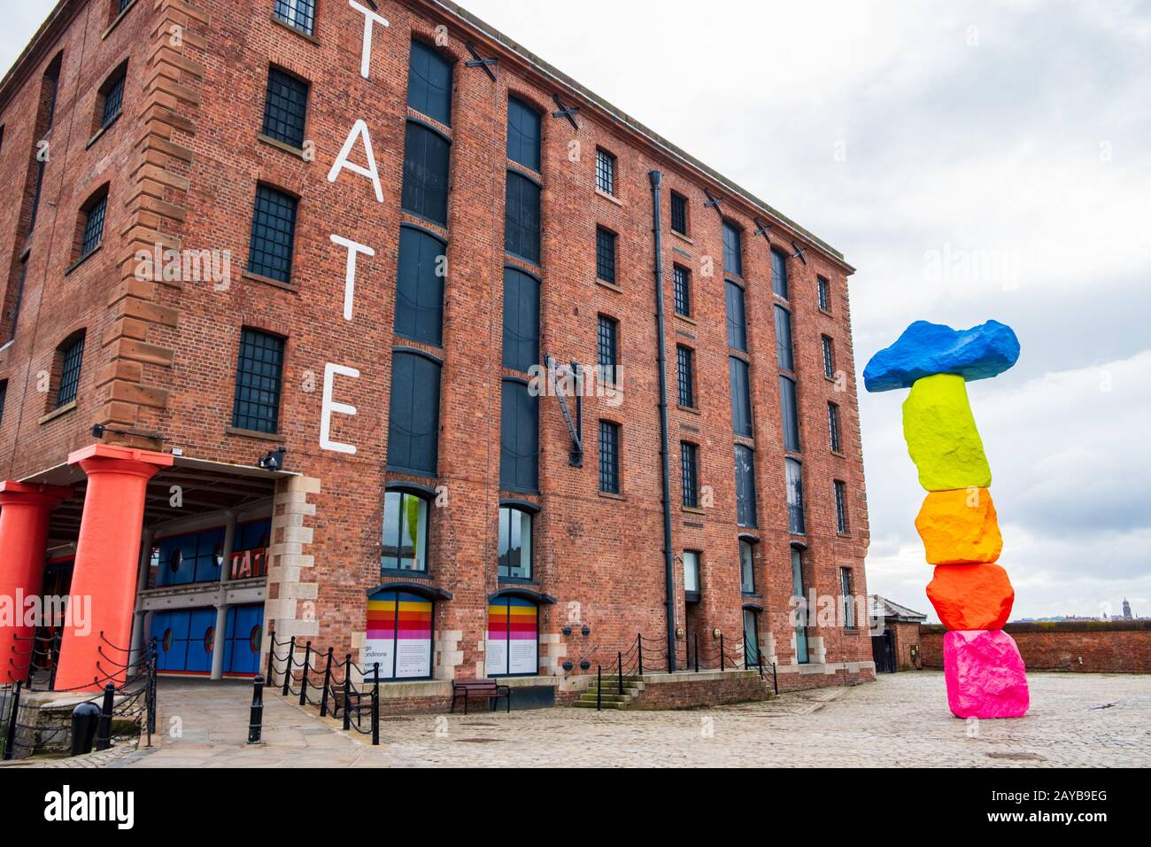 Exterior of Tate Liverpool art gallery in the Albert Dock Area in Liverpool, Merseyside, with a sculpture by Ugo Rondinone named Stock Photo