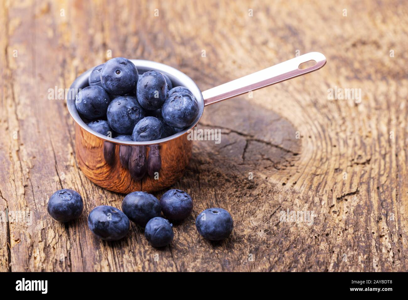 Blueberries in pot on wood Stock Photo