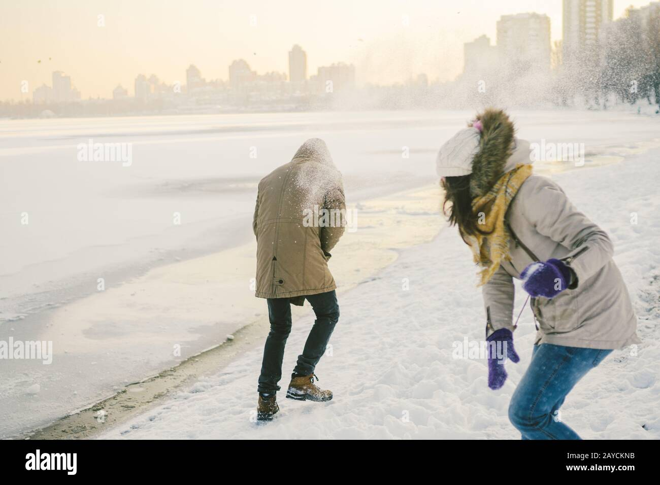 Young Caucasian people in love heterosexual couple have a date in winter near a frozen lake. Active holiday holiday Valentine's Stock Photo