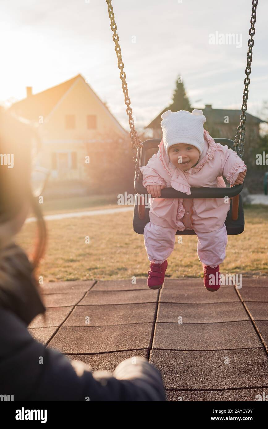 Adorable baby girl with big beautiful eyes and a beanie having fun on a swing Stock Photo