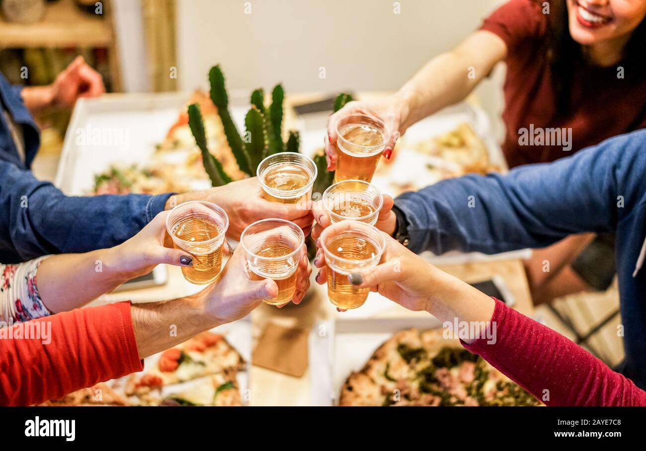 Group of happy friends cheering at home with beer - Young people having fun together eating italian pizza take away - Dinner,party and friendship conc Stock Photo