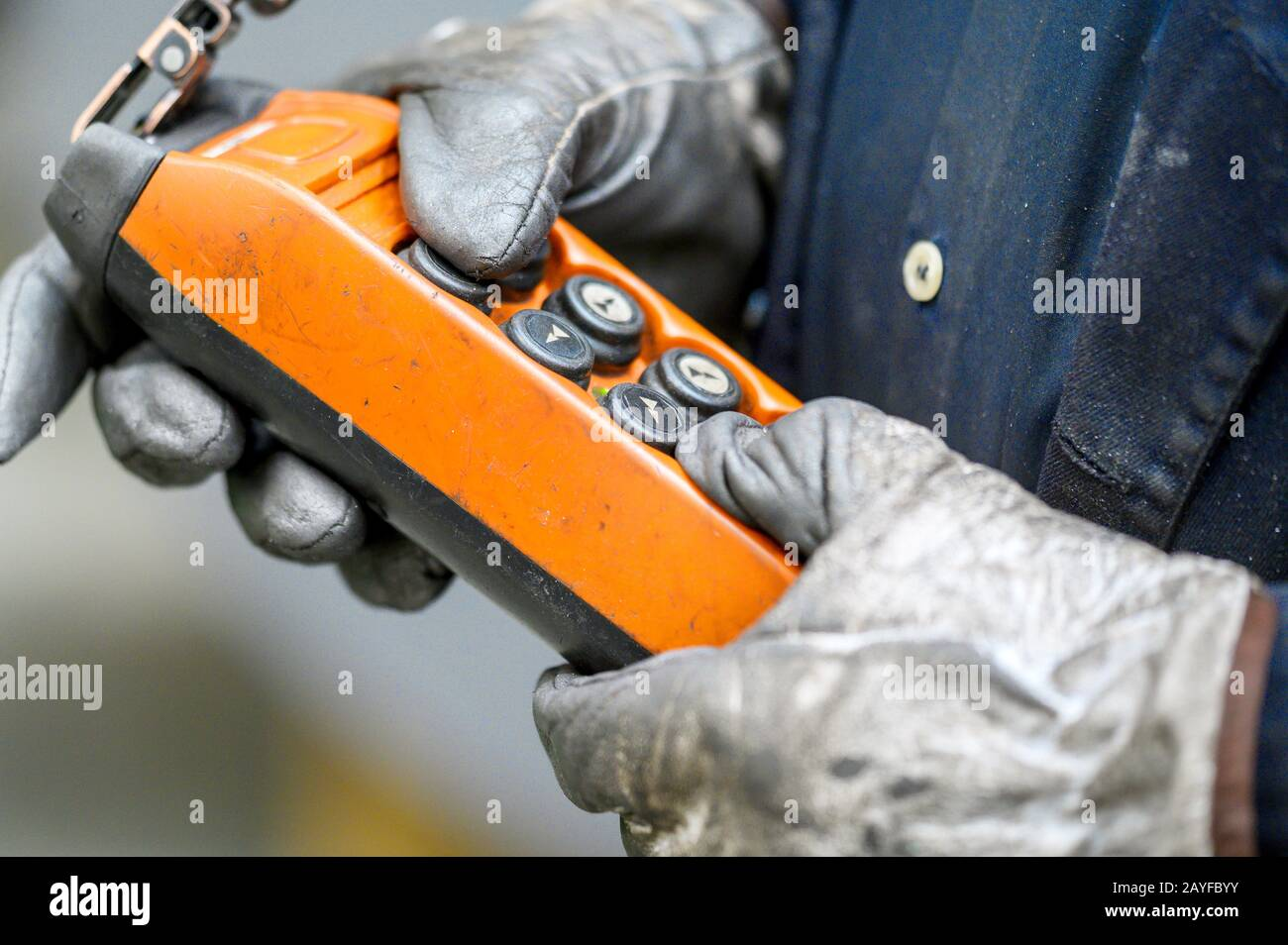 Male hand push remote control switch for overhead crane in the factory, close-up. Electrical control panel of the crane and other lifting equipment in laborer hand . Stock Photo