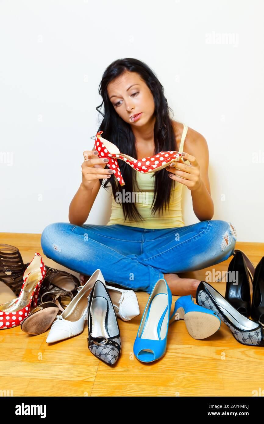 Eine junge dunkelhaarige Frau hat viele verschiedene Schuhe zur Auswahl, MR: Yes Stock Photo