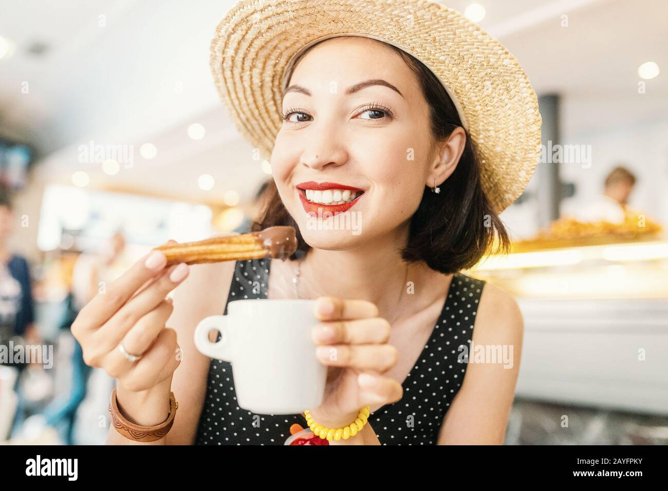 Happy Cheerful girl in hat eating traditional spanish delicious churros, a fried pastry with chocolate in cafe in spain Stock Photo