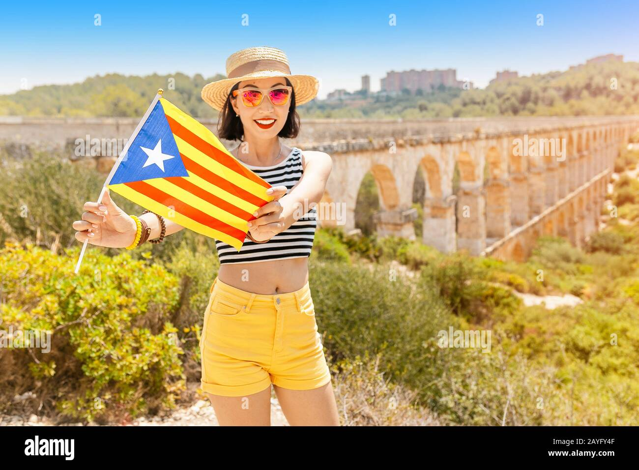 Happy young traveler woman enjoying view of roman Aqueduct Pont del Diable near Tarragona Stock Photo