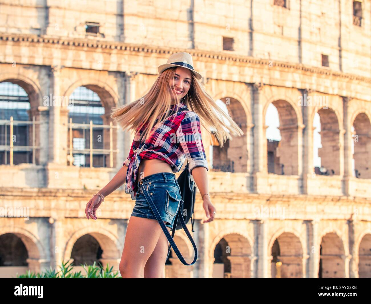 Beautiful young blonde woman with blue at colosseum smiling. Large hat and squared shirt. Rome, Italy Stock Photo