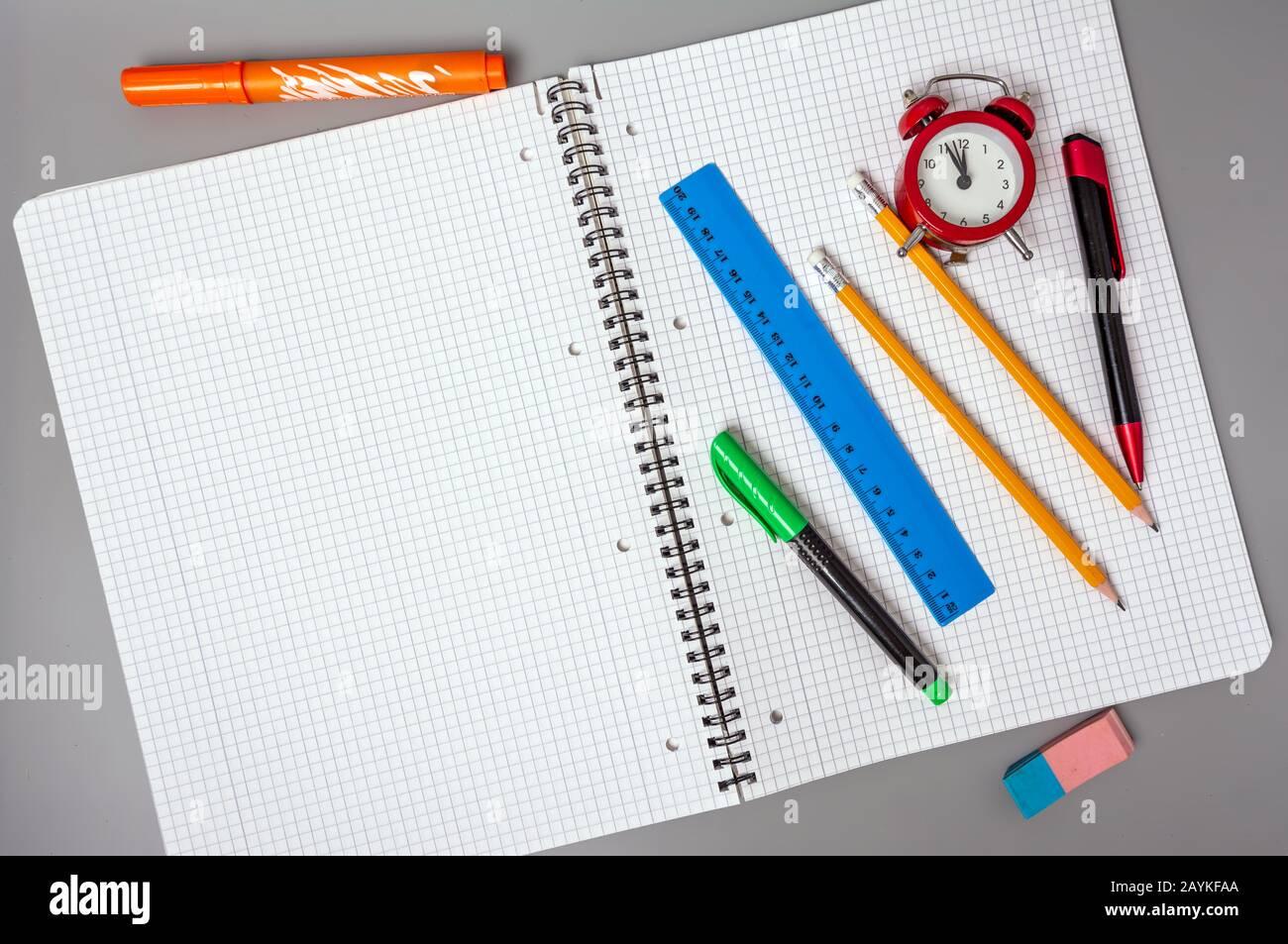 Pencils, a pen and a ruler lie on an open notebook. An alarm clock reminds of time. Office. School supplies. Stock Photo