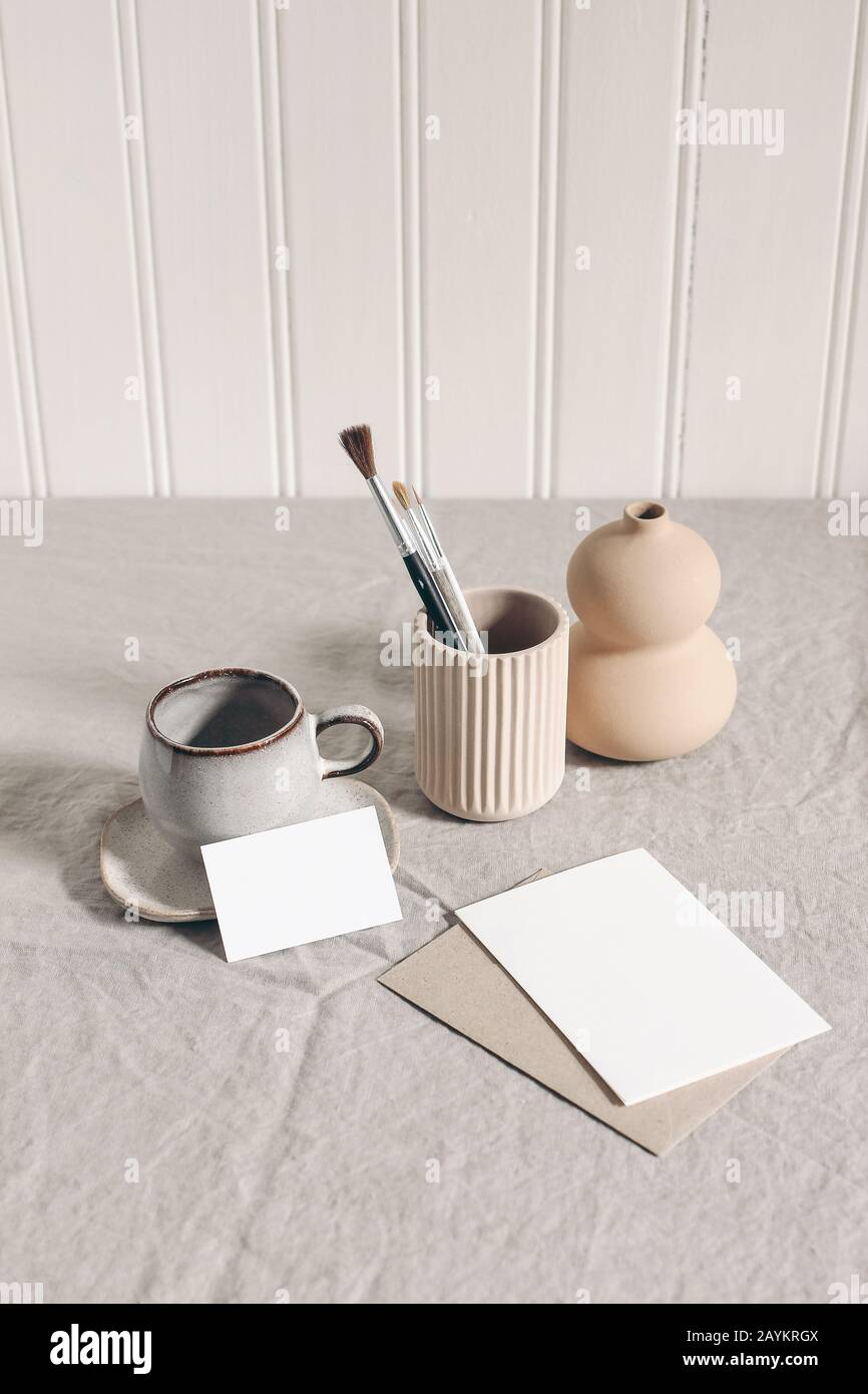 Artistic wokspace, still life. Paint brushes, pencils in ceramic holder, vase, cup of coffee and blank paper card mockups on linen tablecloth. Art sup Stock Photo