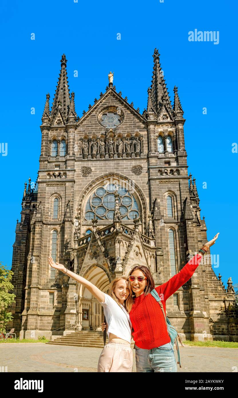 Two girls tourists friends hugging against the background of St. Peter's Church in Leipzig Stock Photo