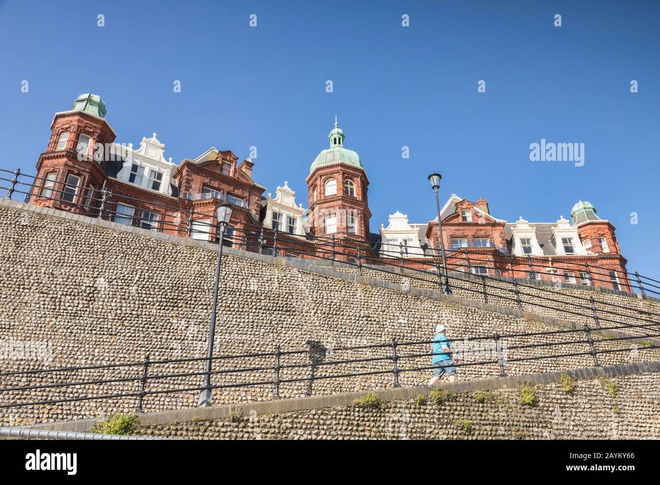 30 June 2019: Cromer, Norfolk, UK - Cobbled sea wall and promenade buildings, one man walking up the zig zag. Clear blue sky. Stock Photo