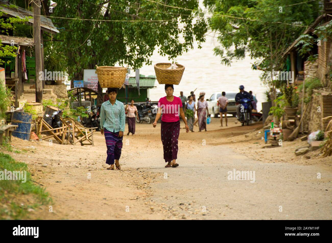 Myanmar women carrying big bamboo basket on their head, walking along the sandy road by the beach in Myanmar Stock Photo