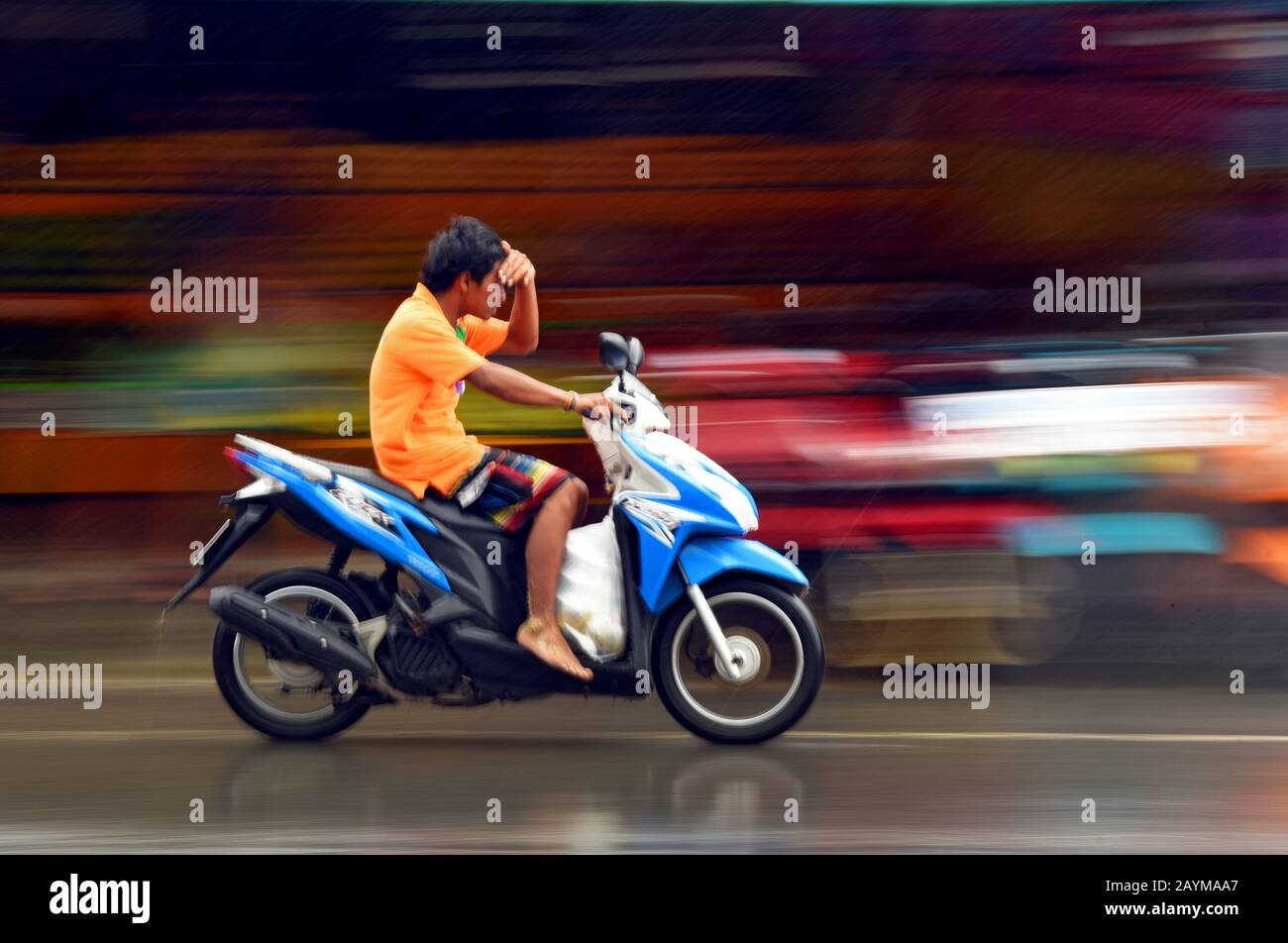 motorcyclist protecting the eyes with the hand against the rain, Thailand, Phuket Stock Photo