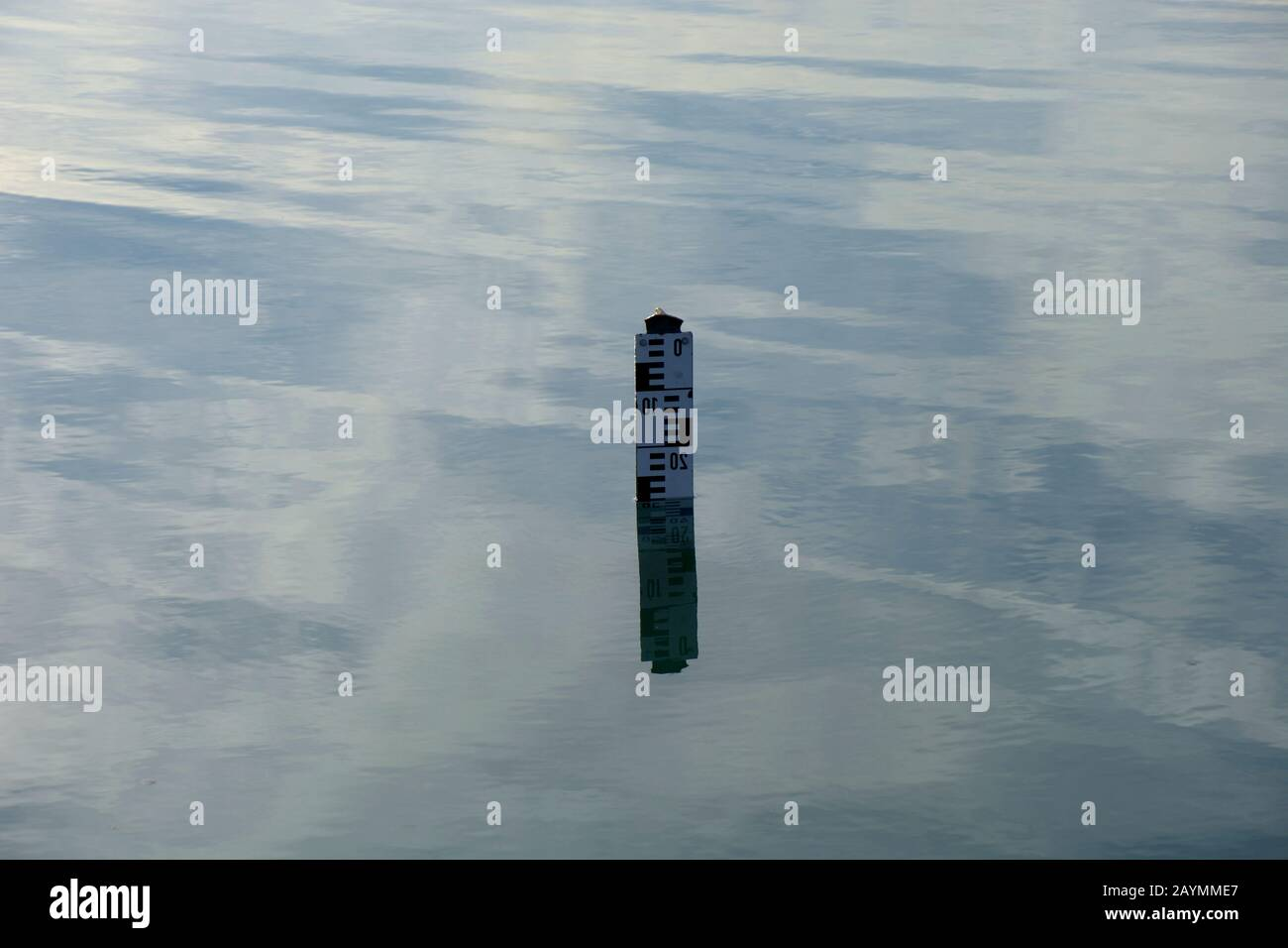 water level indicator show the depth of water in a lake, water depth sign on calm water surface Stock Photo
