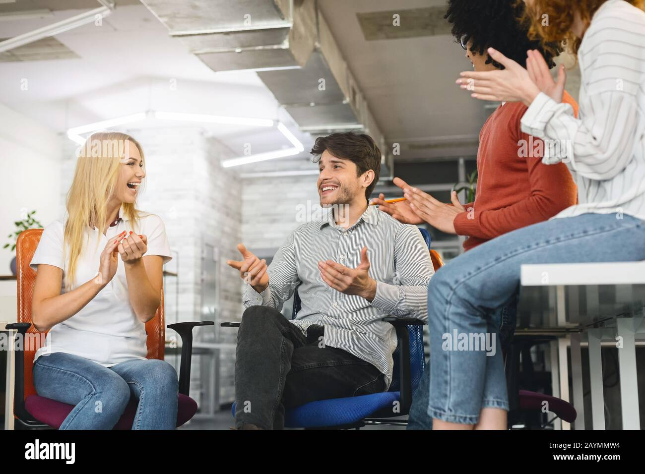 Positive group of colleagues having briefing, laughing and clapping Stock Photo