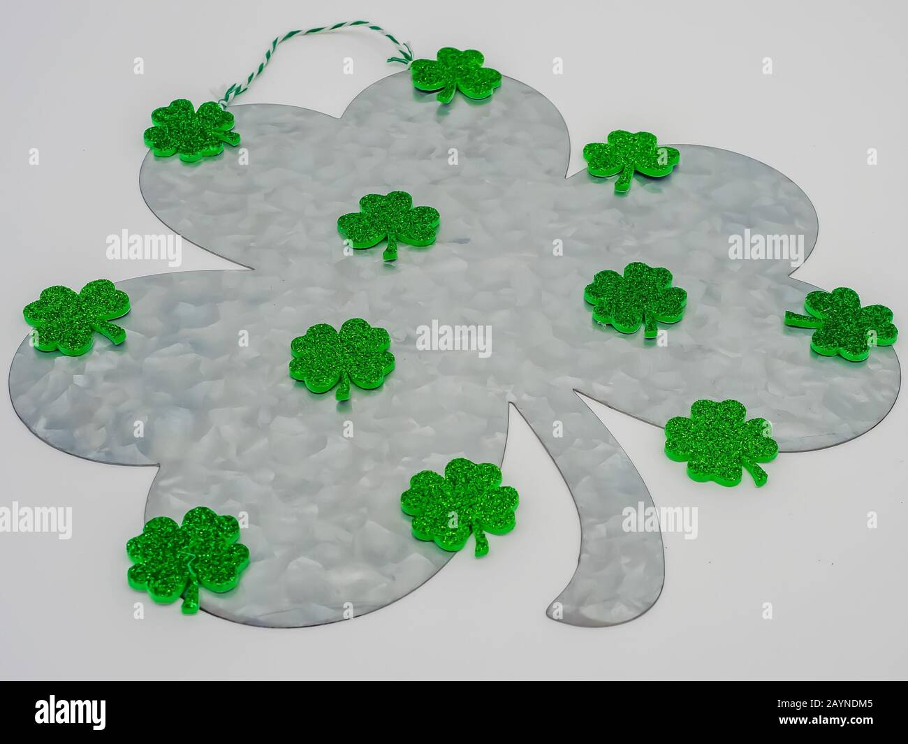 Large rustic metal four clover with small green sparkly four leaf clovers all over it, for St. Patrick's Day. Stock Photo
